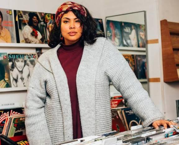 Zangeres Carina Fernandes staat bij platenkast