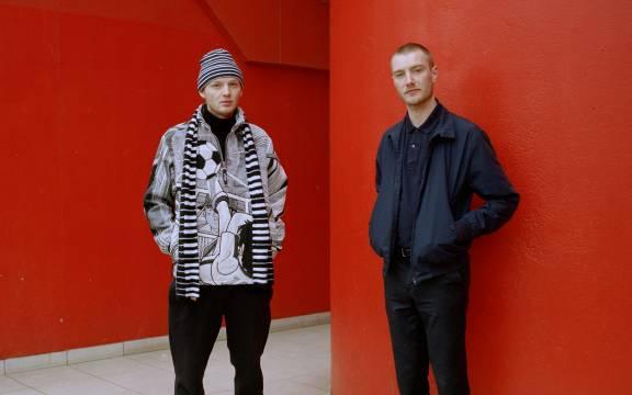 Twee mannen voor rode muur