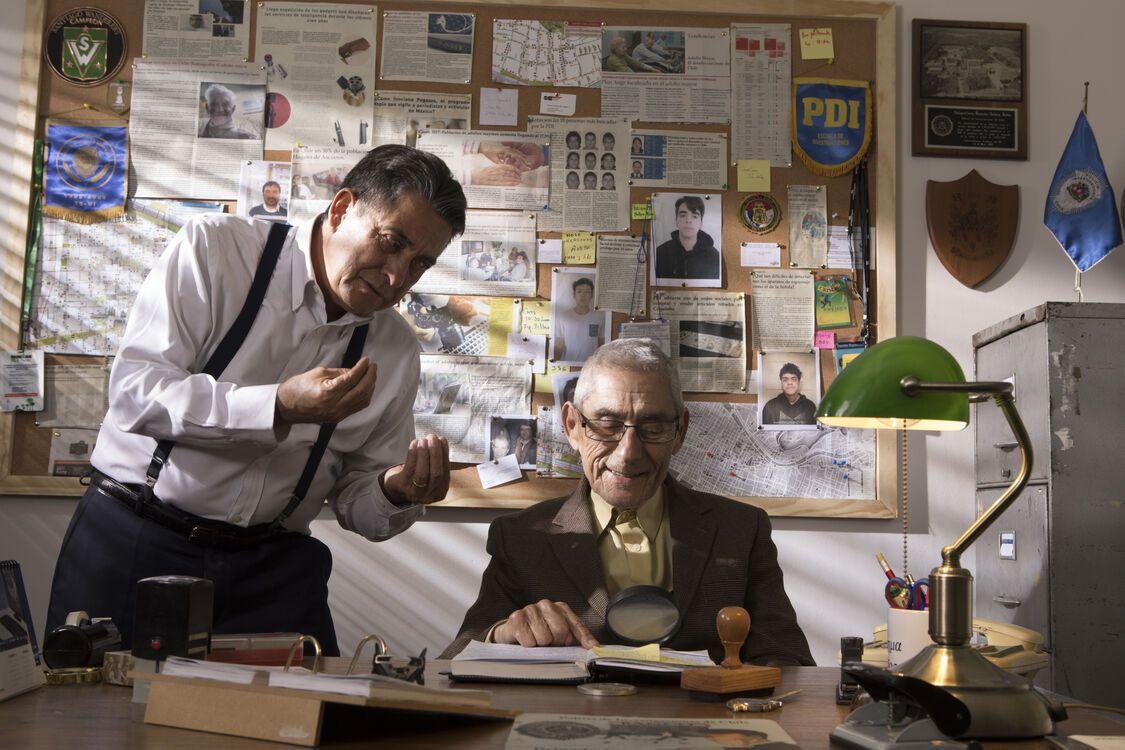 Een volwassen man en oude man bij een bureau